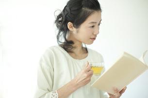 ハーブティーを飲みながら本を読む若い女性の写真素材 [FYI01623673]