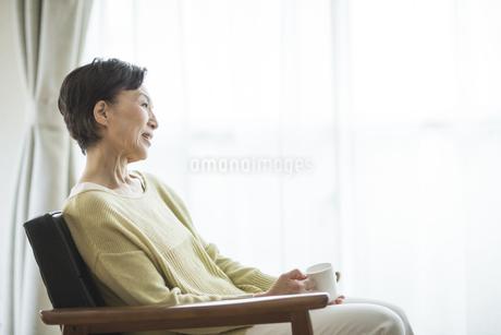 椅子に座る笑顔のシニア女性の写真素材 [FYI01623684]