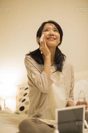 ベッドの上でスキンケアをする女性の写真素材 [FYI01623710]