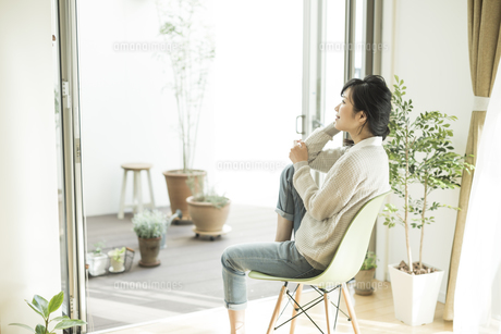 窓辺に座って外を見上げる女性の写真素材 [FYI01623723]