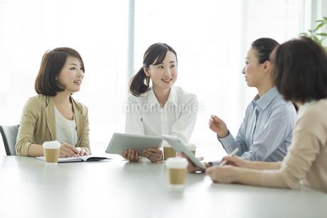 テーブルで打ち合わせをするビジネスウーマンの写真素材 [FYI01623724]
