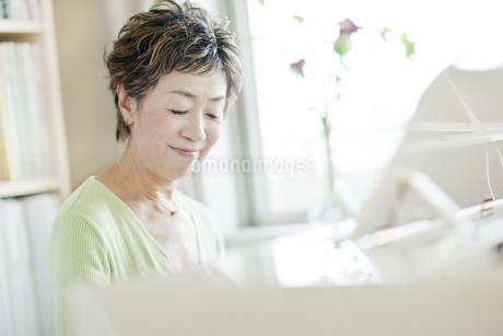 ピアノを弾く中高年女性の写真素材 [FYI01623727]