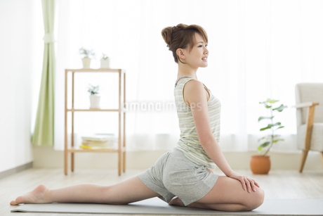 室内でストレッチをする若い女性の写真素材 [FYI01623732]