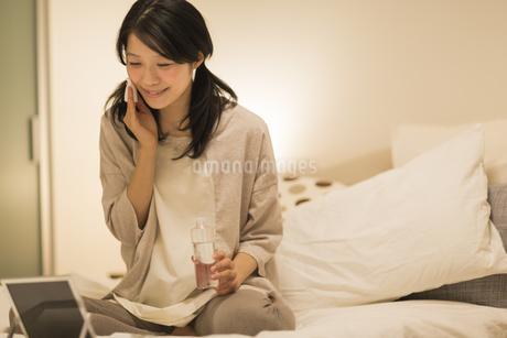 ベッドの上でスキンケアをする女性の写真素材 [FYI01623740]