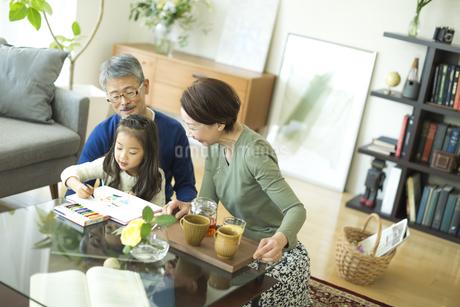 お絵かきをする女の子とシニア夫婦の写真素材 [FYI01623743]