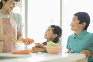 キッチンで料理をする母親に寄り添う子供たちの写真素材 [FYI01623756]