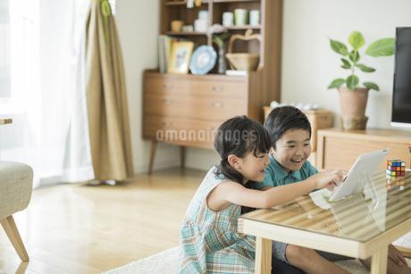 タブレットPCを見る兄と妹の写真素材 [FYI01623765]