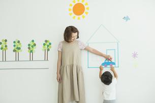壁のイラストの前で遊ぶ親子の写真素材 [FYI01623766]