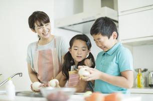 キッチンで玉ねぎの皮を剥く母親と子供たちの写真素材 [FYI01623784]