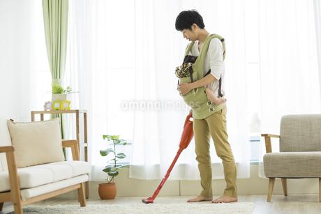 赤ちゃんを抱っこしながら掃除機をかける父親の写真素材 [FYI01623796]