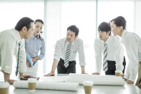 打ち合わせで真剣に話しを聞くビジネスマンとビジネスウーマンの写真素材 [FYI01623798]