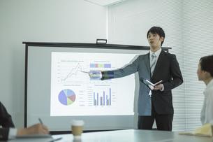 プロジェクターを使用した会議で説明をするビジネスマンの写真素材 [FYI01623826]
