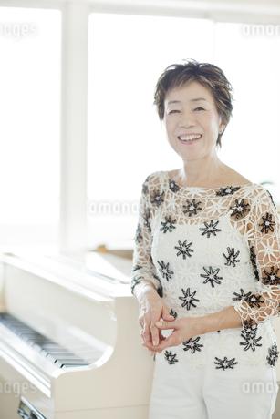 ピアノの横に立つ笑顔の中高年女性の写真素材 [FYI01623846]