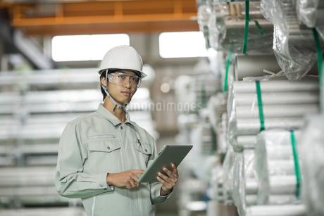 タブレットPCを操作する作業服の男性の写真素材 [FYI01623849]