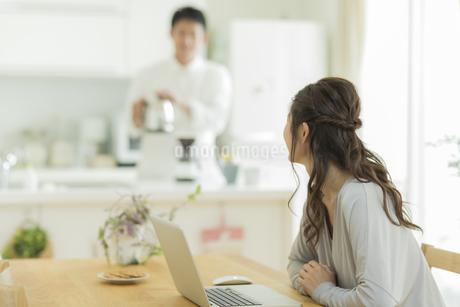 キッチンに立つ夫と会話をする妻の写真素材 [FYI01623851]
