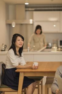 ダイニングテーブルでお茶を飲む娘の写真素材 [FYI01623858]