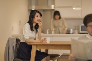 ダイニングテーブルでお茶を飲む娘の写真素材 [FYI01623866]