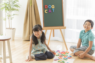 アルファベットで遊ぶ兄と妹の写真素材 [FYI01623870]