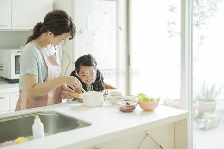 キッチンで料理をする母親に寄り添う女の子の写真素材 [FYI01623883]