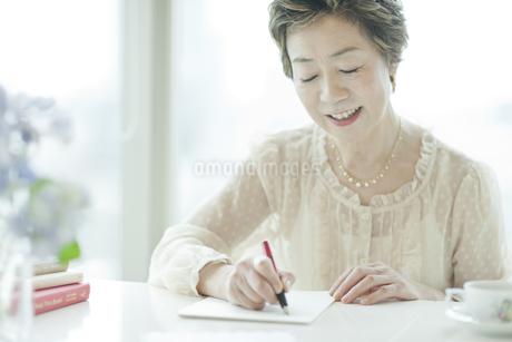 リビングで手紙を書く中高年女性の写真素材 [FYI01623887]