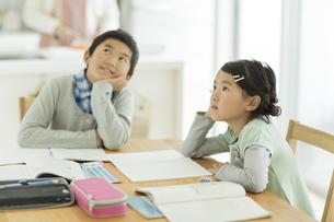 テーブルで勉強をする兄と妹の写真素材 [FYI01623901]