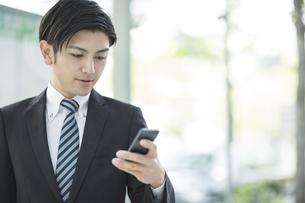 携帯電話を見るビジネスマンの写真素材 [FYI01623906]