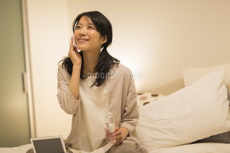 ベッドの上でスキンケアをする女性の写真素材 [FYI01623941]
