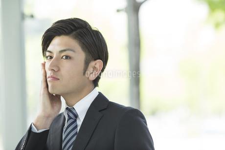 頬に手をあてるビジネスマンの写真素材 [FYI01623942]