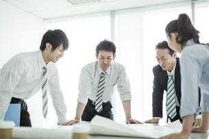 テーブルに図面を広げて打ち合わせをするビジネスマンとビジネスウーマンの写真素材 [FYI01623948]