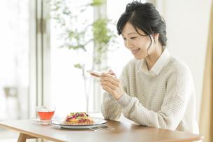 携帯電話でケーキを撮る女性の写真素材 [FYI01623949]