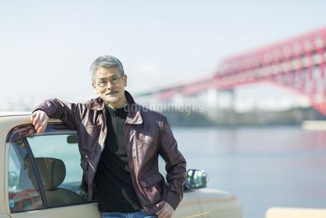 海岸で車に寄りかかるシニア男性の写真素材 [FYI01623957]