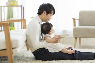 赤ちゃんに絵本を読む父親の写真素材 [FYI01623969]