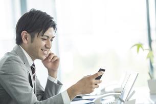 スマートフォンを見るビジネスマンの写真素材 [FYI01623974]