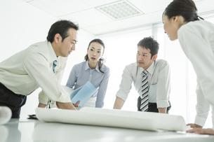 テーブルに図面を広げて打ち合わせをするビジネスマンとビジネスウーマンの写真素材 [FYI01623987]
