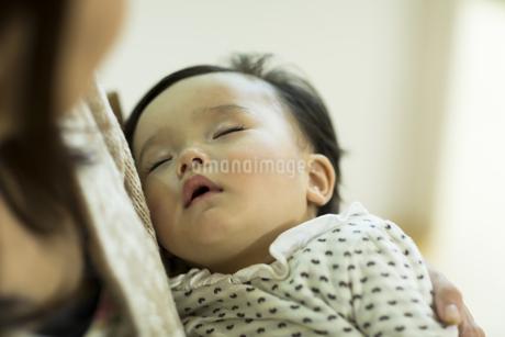 母親に抱っこされて眠る赤ちゃんの写真素材 [FYI01623998]