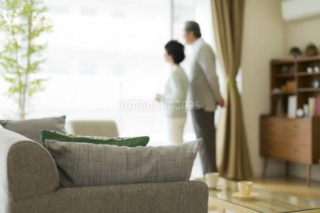 窓辺に立ち外を眺めるシニア夫婦の写真素材 [FYI01624006]