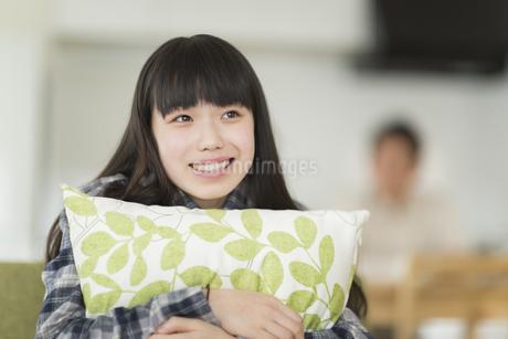 ソファーに座ってクッションを抱える女の子の写真素材 [FYI01624007]