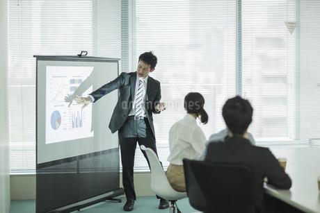 プロジェクターを使用した会議で説明をするビジネスマンの写真素材 [FYI01624025]