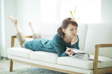 ソファに寝転んで雑誌を読む女性の写真素材 [FYI01624032]