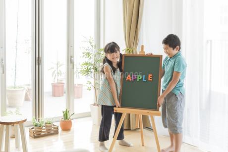 アルファベットを並べた黒板の横に立つ兄と妹の写真素材 [FYI01624036]