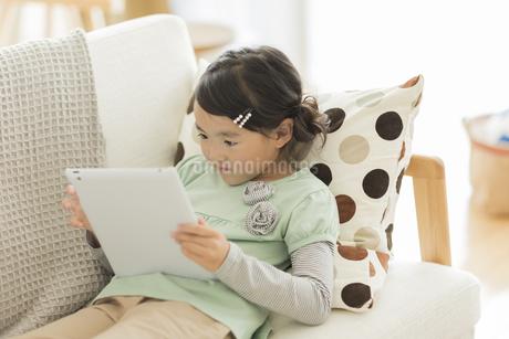 ソファーでタブレットPCを見る女の子の写真素材 [FYI01624042]