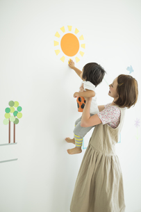 壁のイラストの前で遊ぶ親子の写真素材 [FYI01624044]