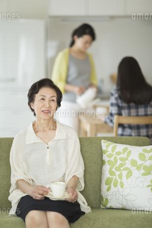 ソファーに座りお茶を飲む祖母の写真素材 [FYI01624048]