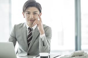 デスクに座るビジネスマンの写真素材 [FYI01624050]