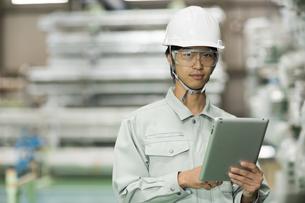 タブレットPCを持つ作業服の男性の写真素材 [FYI01624084]