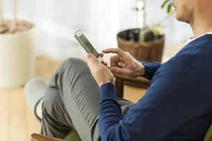 スマートフォンを操作するシニア男性の手元の写真素材 [FYI01624088]