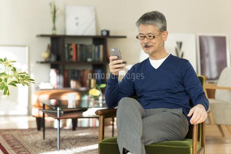 スマートフォンを操作するシニア男性の写真素材 [FYI01624098]