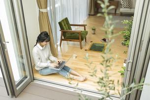 窓辺でパソコンをする若い女性の写真素材 [FYI01624100]