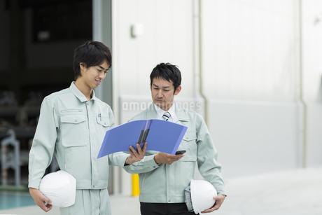 打ち合わせをする2人の作業着の男性の写真素材 [FYI01624110]