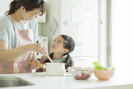 キッチンで料理をする母親に寄り添う女の子の写真素材 [FYI01624112]